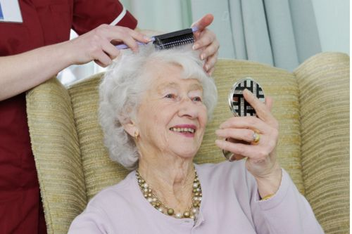 Care worker helps her elderly patients get ready by combing her hair for her